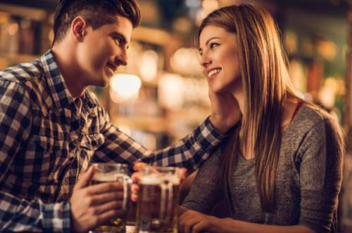 Affectionate young couple drinking in a bar